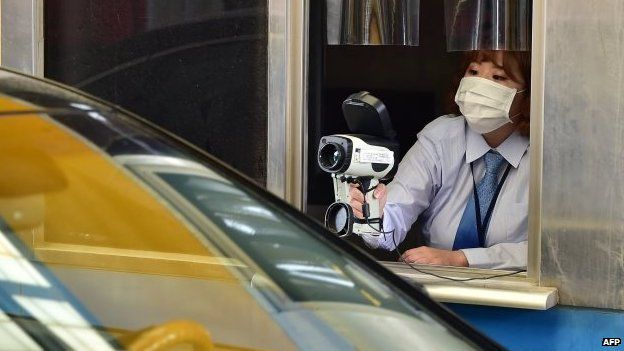 South Korean border worker checks driver's body heat