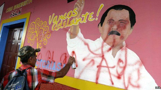 A man sprays graffiti on a mural during a demo against a planned canal in Nicaragua