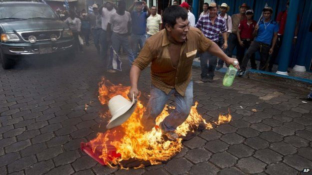 A protester burns a flag of Nicaragua's ruling party during a rally against a planned canal