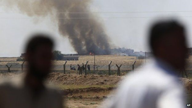 People look from the Turkey-Syria border at smoke rising after a US-led air strike on IS militants in the Syrian town of Tal Abyad (15 June 2015)