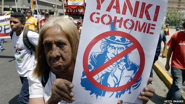 A supporter of Venezuelan president Nicolas Maduro holds a poster of Uncle Sam to protest against the United States, during a demonstration in Caracas on 12 March, 2015.