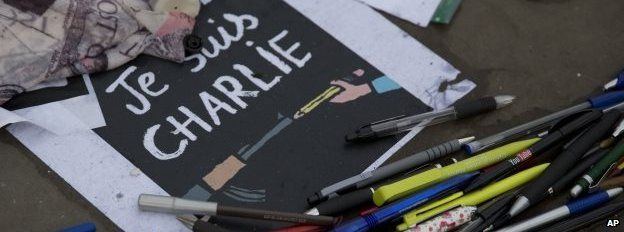 """Pens and pencils lay in a circle around """"I am Charlie"""" posters in Trafalgar Square, London, on 9 January 2015"""
