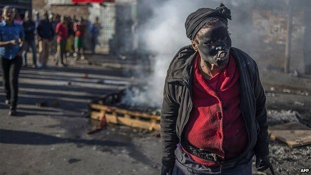 A woman covered in soot gestures and shouts towards foreign nationals outside the Jeppies Hostles, in the Jeppestown area of Johannesburg, on April 17, 2015