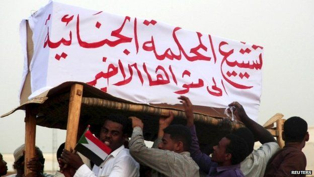 Supporters of Sudanese President Omar al-Bashir (not in the picture) carry a mock coffin representing the International Criminal Court at the airport in the capital Khartoum, Sudan, 15 June 2015