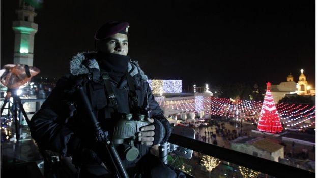 Cảnh sát Palestine đứng gác ở Quảng trường Manger, cạnh Nhà thờ Chúa giáng sinh khi người dân Palestine tập trung trong đêm Noel tại thành phố Bethlehem, ở Bờ Tây hôm 24/12/2017.