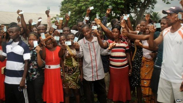 Voters show their cards, ahead of the vote for the presidential elections in Gokana, 28 March 2015