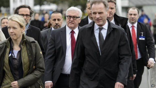 German Foreign Minister Frank-Walter Steinmeier, center, walks outside the hotel during negotiations on Iran's nuclear program between Iran and world powers in Lausanne, Switzerland, 29 March 2015