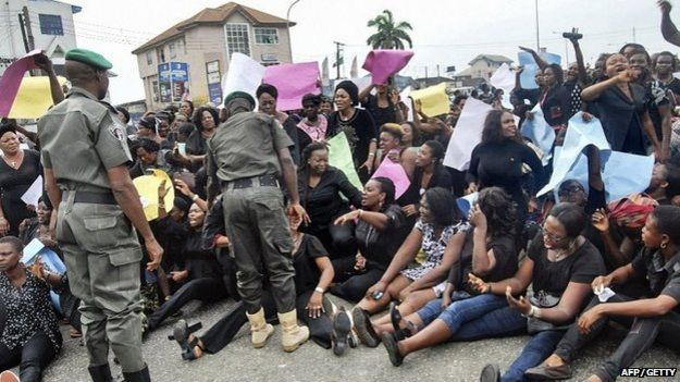 All Progressives Congress (APC) party supporters sit on the floor during a march towards the Independent National Electoral Commission Office in Port Harcourt calling for the cancellation of the presidential elections in the Rivers State on 30 March 2015