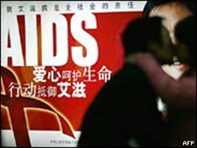 Pareja frente a afiche de la campaña china contra el SIDA