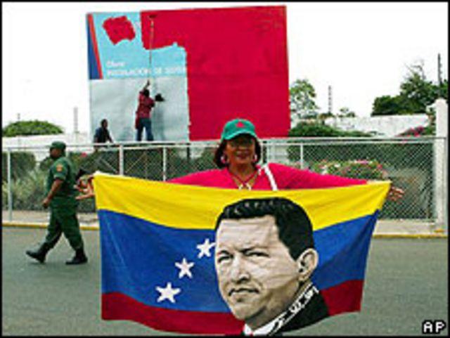 Mujer parada frente al puerto de Maracaibo sostiene bandera con la imagen de Hugo Chávez