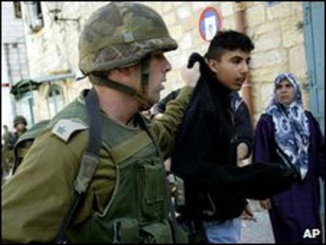 Soldado israelí con ciudadano palestino