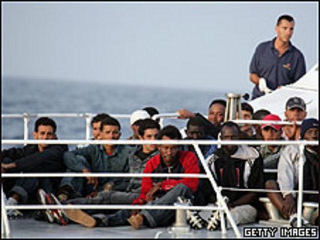 Inmigrantes africanos con guardacostas italianos