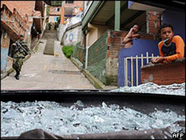 Soldado colombiano pasa por un auto destruido por las balas en el barrio de Santo Domingo Savio en Medellín.