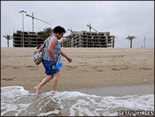 Una mujer camina por la playa; construcciones abandonadas detrás