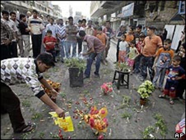 Personas dejando dulces y flores en el escenario de un ataque en Bagdad, 24 abril 2009