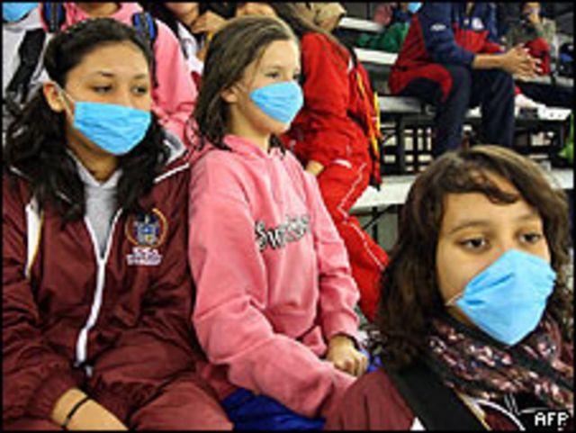 Mexicanos vistiendo máscaras para evitar brote de gripe porcina.