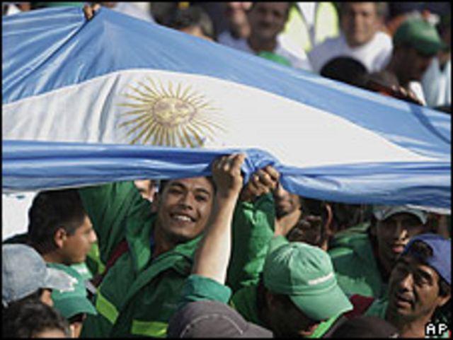 Trabajadores argentinos levantan una bandera durante manifestación en Buenos Aires