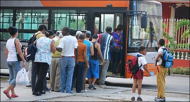 Cubanos haciendo fila para subir a un autobús
