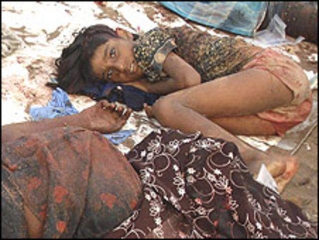 Niño tamil junto a cadáveres tras un ataque del gobierno (Foto: del sitio Tamilnet)