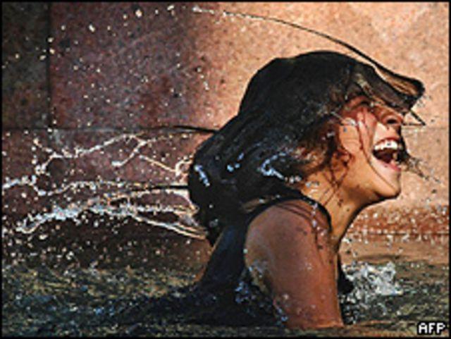Niña toma un baño en una fuente de Santiago