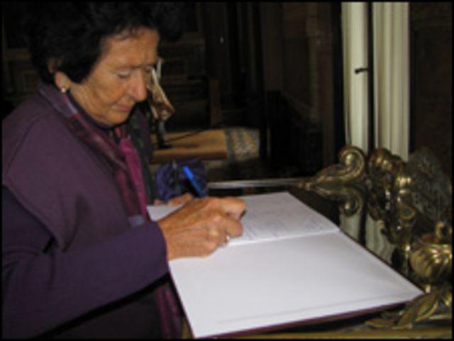 Lectora firma el libro de condolencias.