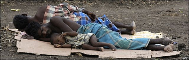 Refugiados tamiles descansan sobre cartones