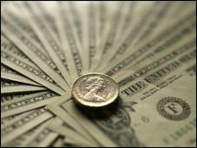 Moneda de libra sobre billetes de dólar.