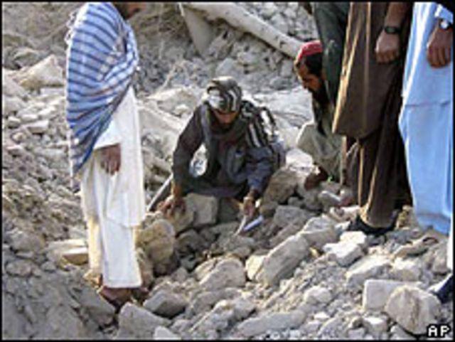 Hombres conversan entre los escombros tras ataque aéreo en Farah