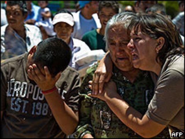 Familiares de una víctima lloran en el cementerio.