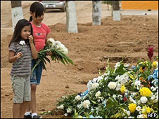 Niñas ponen flores durante el funeral por los fallecidos en guardería de Sonora