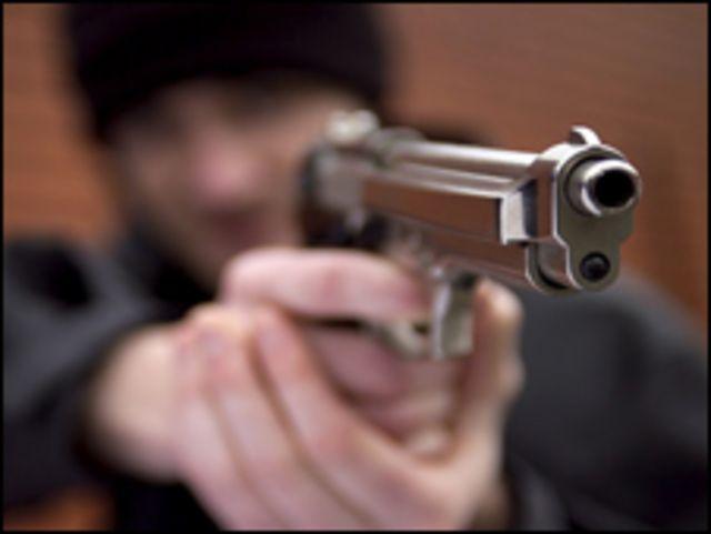 Joven apunta con una pistola.