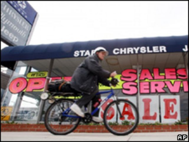 Ciclista pasa delante de concesionaria de Chrysler en venta