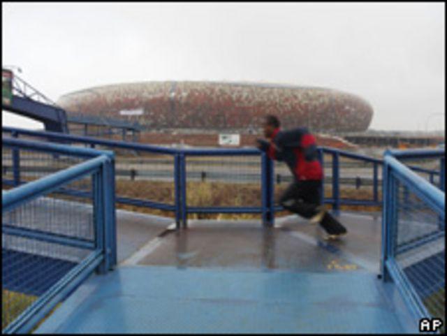 Un joven hace deporte ante el nuevo estadio de Johannesburgo.