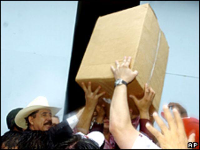 El presidente de Honduras, Manuel Zelaya, con sombrero, dirige a sus seguidores al recoger cajas en una base de la fuerza aérea en Tegucigalpa