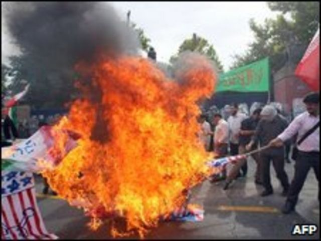 Estudiantes iraníes queman banderas británicas y de EE.UU., durante una protesta fuera de la embajada británica en Teherán el 23 de junio de 2009