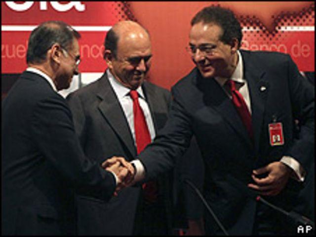 Ali Rodriguez, izquierda, da la mano al ex  presidente del banco de Venezuela, Michel Goguikian