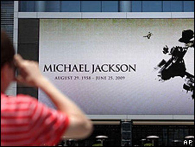 Un peatón toma fotos de un letrero en el Staples Center de Los Ángeles donde se celebrará el acto de despedida de Michael Jackson