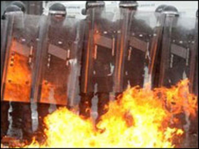 قوات الشرطة تحاول تجنب النيران خلال الاضطرابات