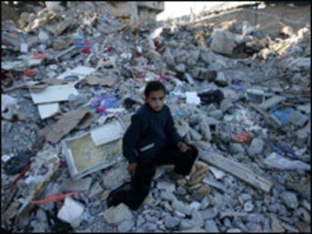 طفلة من غزة تمر عبر المباني المدمرة