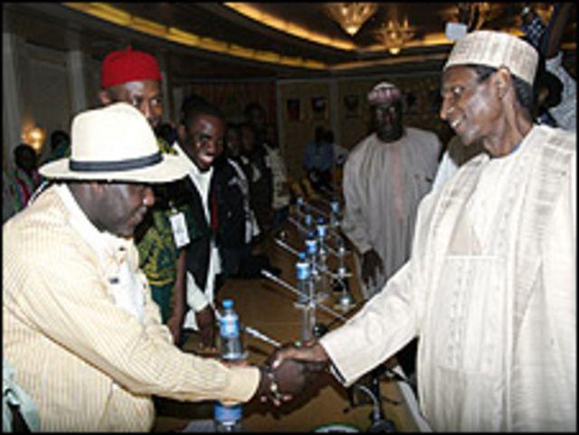 الرئيس النيجيري يصافح أحد قادة المتمردين