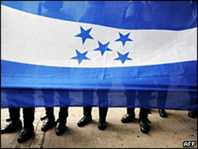 Agentes antimotines detrás de una bandera hondureña