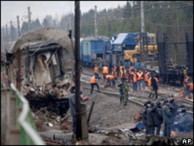 Investigadores y trabajadores de rescate se ven en medio de los restos del tren