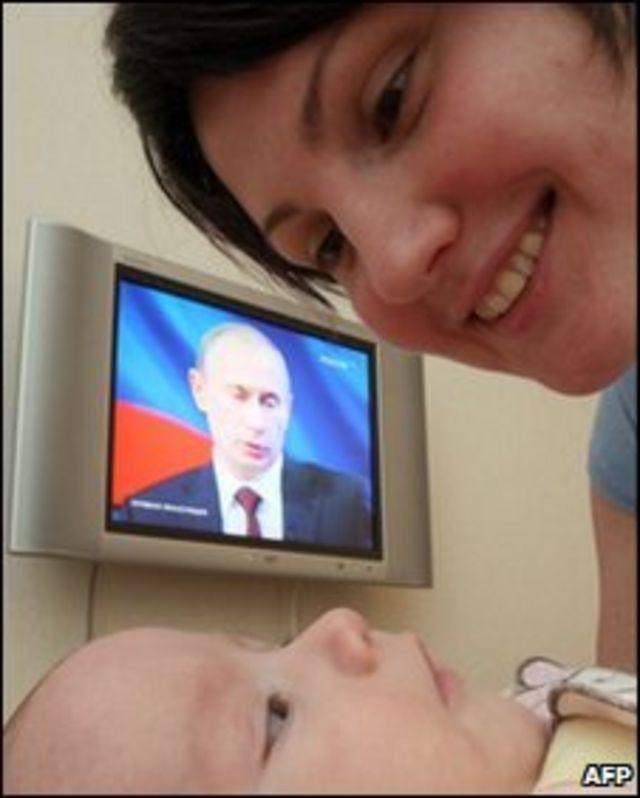 Женщина склонилась над около экрана телевизора, показывающего премьер-министра России Владимира Путина (архивное фото)
