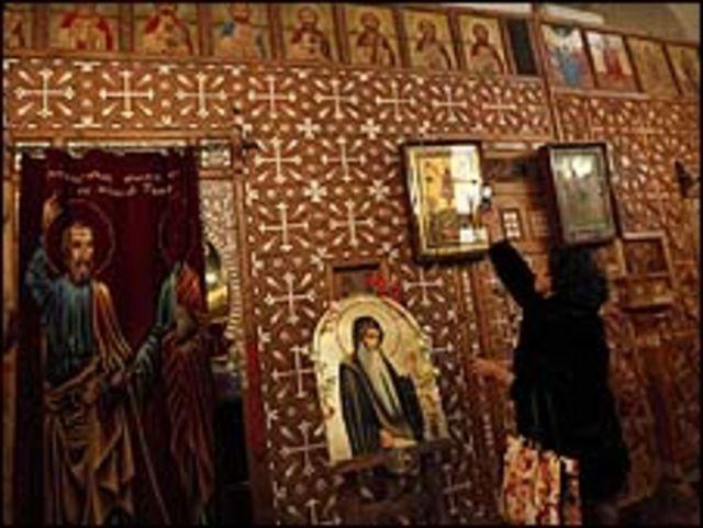سيدة تلتقط صورة بهاتفها المحمول داخل الدير