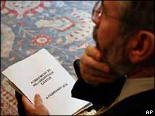 El presidente del Sinn Fein, Gerry Adams, sostiene una copia del acuerdo.