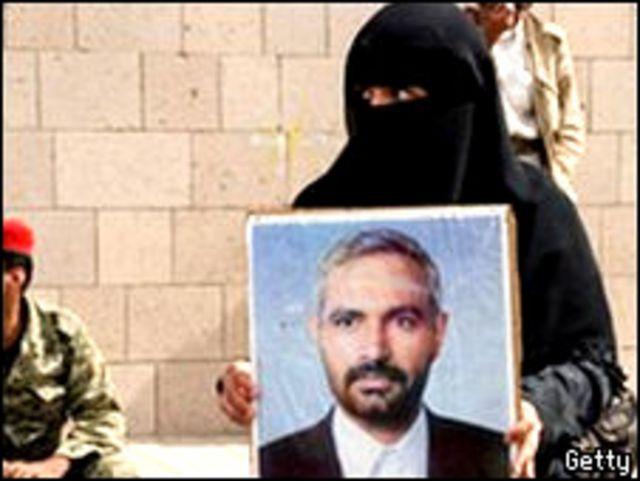 سيدة تحمل صورة الصحافي اليمني محمد المقالح