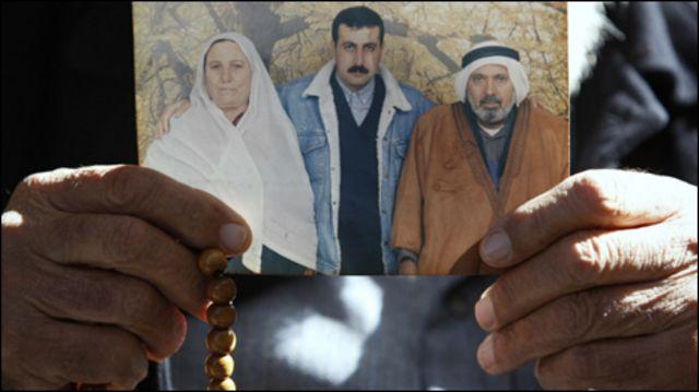 والد محمود عبد الرؤوف المبحوح يحمل صورة للعائلة في مخيم جباليا شمالي قطاع غزة