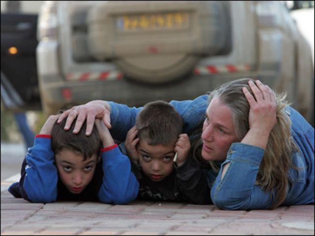 أم إسرائيلية تحاول حماية طفليها من الصواريخ التي تنطلق من غزة