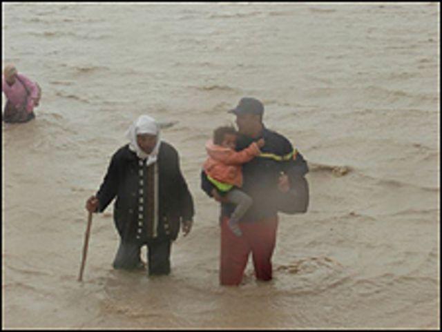 عنصر من الوقاية المدنية يساعد اسرة في عبور مياه الفيضانات