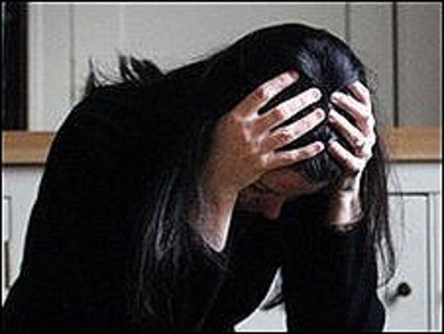 امرأة تضع رأسها بين يديها